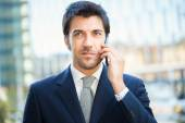 Handsome businessman talking on the mobile phone — Stock Photo