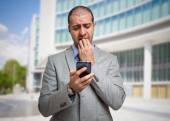 Scared man looking at his mobile phone — Stock Photo