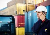 Worker in front of a stack of containers — Stock Photo