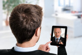 Man using his tablet to speak to a colleague — Stock Photo