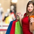 Portrait of a woman in red dress holding shopping bags — Stock Photo #61563243