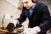 Worker using grinding machine — Stock Photo