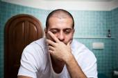 Tired man looking in mirror — Stock Photo