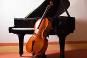 Violin leaning on piano — Stock Photo