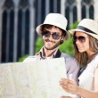 Couple of tourists holding map — Stock Photo #63268933