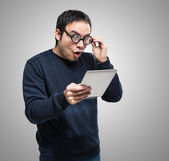 Surprised nerd looking at tablet — Stock Photo