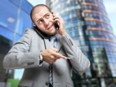 Businessman talking on many phones — Stock Photo