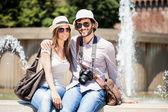 Tourists sitting near fountain — Stock Photo