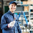Worker in shop holding wrench — Stock Photo #67067581