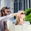 Couple of tourists holding map — Stock Photo #67629615