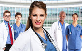 Smiling doctor in front of medical workers — Stock Photo