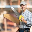 Carpenter holding wood plank and saw — Stock Photo #68240353