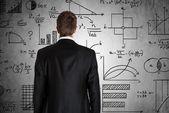 Empresario frente a las fórmulas matemáticas — Foto de Stock