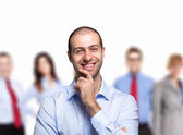 Smiling man in front of people — Stock Photo