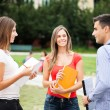 Three students talking in a park — Stock Photo #71381829