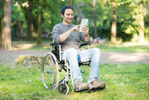Man using tablet in wheelchair — Stockfoto