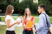 Three students talking in a park — Stock Photo
