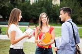 Three students talking in a park — Stockfoto