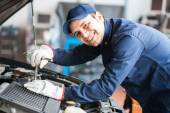Smiling fixing a car engine — Stock Photo