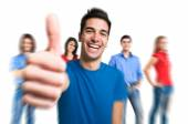 Happy man giving thumbs up in front of a group of people — Stockfoto