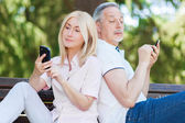 Mature couple using phones — Stock Photo