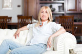 Woman relaxing on couch in home — Stock Photo
