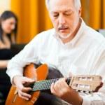 Mature man playing  guitar — Stock Photo #76739059