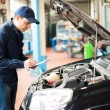 Mechanic writing on a clipboard — Stock Photo #76738915