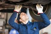 Mechanic checking condition lifted car — Stock Photo