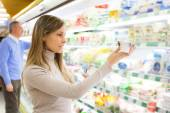 Woman taking product in supermarket — Stock Photo