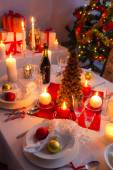 Many gifts near a Christmas tree in the candlelight — Stock Photo