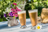 Coffee latte in a sunny garden — Stock Photo