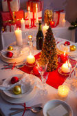 Christmas dishware on the white and red table — Stock Photo