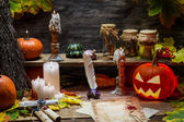 Table in witch hut with halloween pumpkin — Stock Photo