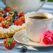 Close-up on coffee and tart with strawberries and blueberries — Stock Photo #53486275