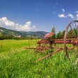 Red rake in a field in the mountains — Stock Photo #54001789