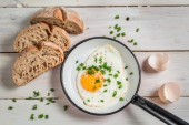 Fried egg with chives served with bread — Stock Photo