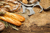 Various kinds of whole wheat bread on old wooden table — Stock Photo