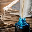 White feather on blue inkwell and old book — Foto de Stock   #54327101