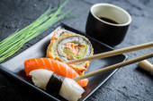 Sushi in a black ceramic eaten with chopsticks — Stock Photo