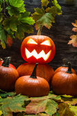 Jack o lantern on pumpkins pile with leaves — Stock Photo