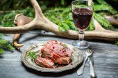 Red wine in a glass and venison on a plate — Stock Photo