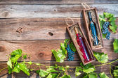 Wines in a wooden box and grapes — Stock Photo