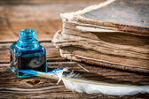 White feather on blue inkwell and old book — Stock Photo