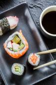 Sushi on black ceramic eaten with chopsticks — Stock Photo