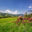 Red rake in a field in the mountains — Stock Photo #58831431