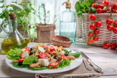 Spring salad in a sunny kitchen full of vegetables — Stock Photo