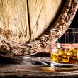 Whiskey glass and old oak barrel — Stock Photo #65126429