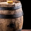 Glass of aged brandy or whiskey on the rocks and old oak barrel — Stock Photo #65126557