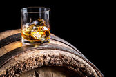 Glass of whisky with ice on old wooden barrel — Stockfoto
